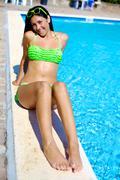 happy female model in bikini laying on swimming pool - stock photo
