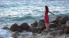 Attractive woman standing on seaside rocky shore, open arms, feel wild nature 4K Stock Footage