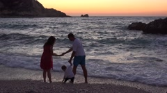 Happy family throwing stones in sea, wave covering soles, sunset sky 4K - stock footage