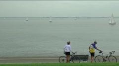 Bikers are biking along the coast of Den Helder Stock Footage