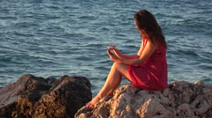 Beautiful young woman sitting on cliff searching on tablet pad, sea wave   Stock Footage