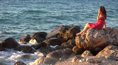 Stock Video Footage of Gorgeous sea scenery, beautiful woman sitting on rocky shore enjoy nature