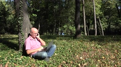 4K. Man in park sitting, making a phonecall and using a laptop, PC. Stock Footage