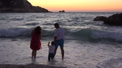 Child and parent have fun together  throwing off stones in sea, sunset sky  Stock Footage