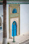 A blue door with black studs and stone ornament at doorway in tunisia Kuvituskuvat