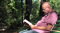 Men Reading Literature Book Sitting on Park Bench Natural Environment Outdoor Stock Footage