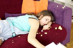 Sleepy teenager after having done mess with chips and pop corn Stock Photos