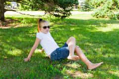 smiling girl in sunglass with sore knee - stock photo