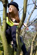young teenager sitting on tree thinking smiling - stock photo