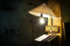 Menu in cafe under light of bulb in rice hat. Stock Photos