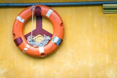 Orange old lifebuoy with rope attached to wall. Stock Photos