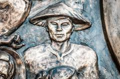 part of monument with man in hat in vietnam, asia. - stock photo