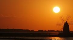 Windmill at sunset: sky, sun, yellow, salt pans of Trapani, Sicily, Italy Stock Footage