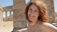 Smiling beautiful woman near greek temple in Sicily: Italian, summer, sun, heat Stock Footage