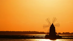 Windmill at sunset: sky, sun, yellow, salt pans of Trapani, Sicily, Italy Stock Footage