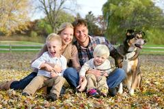 Happy family and pet dog autumn portrait Stock Photos