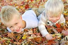 Two young children playing in fall leaf pile Stock Photos