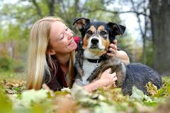 woman relaxing with her german shepherd dog on fall day - stock photo