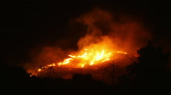 A bushfire burning orange and red at night - stock footage