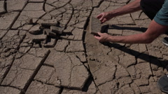 4K Geologist Studies Cracked Earth Or Mudcracks Stock Footage