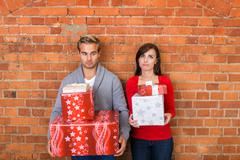 Frowning lovers holding christmas gifts Stock Photos
