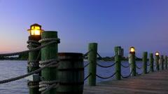 Lamps light boardwalk around lake - stock footage