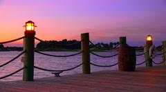 Lamps illuminate boardwalk around lake at sunset Stock Footage