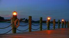 Lamps light boardwalk.  Lens flare.  Dusk. Stock Footage