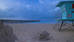 1080p Time lapse, Sunrise on beach with pier and lifeguard tower Stock Footage