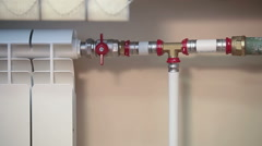 Hand touching cold radiator and turning on valve on pipe for supplying hot water Stock Footage