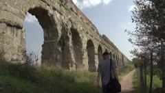 Tourist (released) views scenic aqueduct Claudia, Rome 4k Stock Footage