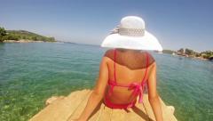 4k, little girl with straw hat and bikinni is sunbathing on sea wodden dock, Stock Footage