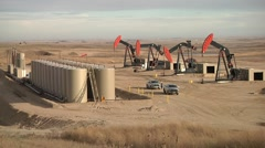 4 Pumping Units With Tanks Wide Shot - stock footage