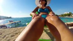 4k crane shoot of attractive female sunbathing on summer beach, wide shoot Stock Footage