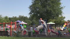 Active children with families in playground, amusement in summer season, playing Stock Footage
