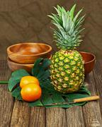 Still life with pineapple and oranges on wooden background. Stock Photos
