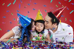 two parents kiss their child in birthday party - stock photo