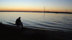 A fisherman relaxes on a quiet and peaceful waterway in South Carolina - stock footage