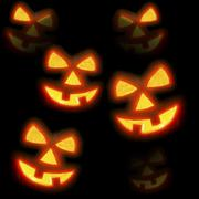 lots of pumpkins lit brightly against a black - stock photo