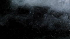 White flickering bubbles and ink moving in space, on black background Stock Footage
