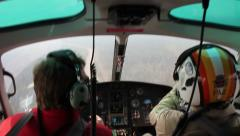 Two helicopter pilots pointing and following dirt road while in flight Stock Footage