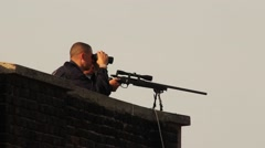 Two snipers aiming large gun and looking through goggles on roof top Stock Footage