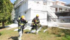 Two firemen running by the camera covered in white foam at house fire Stock Footage