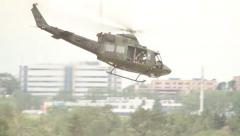 Soldiers on board army helicopter releasing cable from mechanical hook Stock Footage
