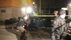 Police negotiators run while carrying a child hostage into an ambulance Stock Footage