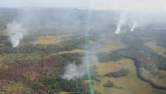 In flight aerial view of smoke columns in widespread forest fire Stock Footage