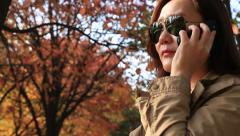 Pan right shot of Asian woman on black sunglasses talking on the phone Stock Footage