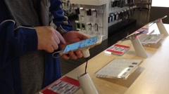 People playing with new iphone inside apple store Stock Footage