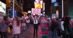 "Young man activist sign ""TV is brain washing"" on Times Square in NYC at night. Stock Footage"