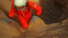 Astronaut climbing rocks rock mars Stock Footage